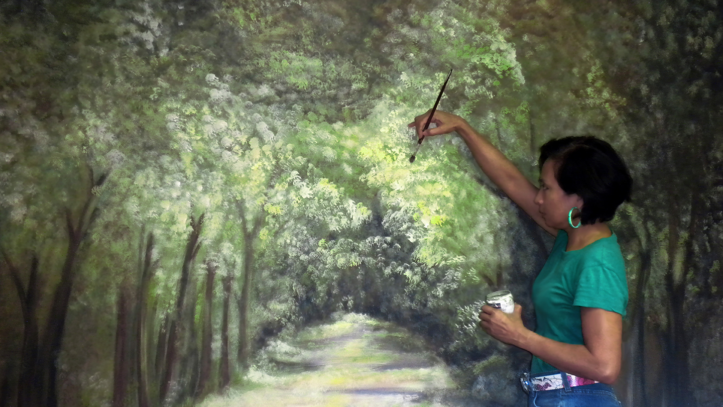 Cynthia Llanes painting a mural called Secret Garden